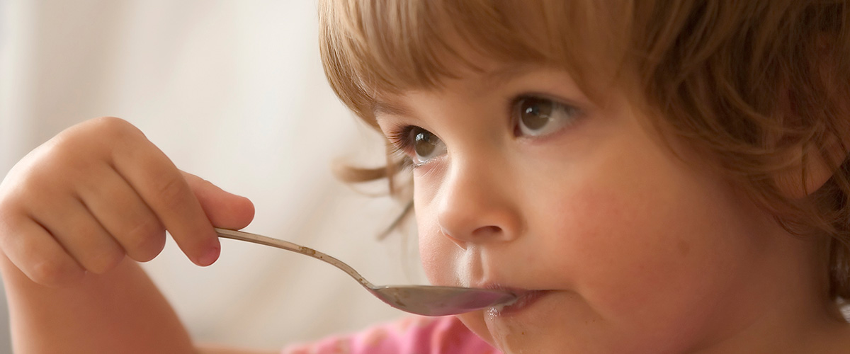 A little girl eating food with a spoon